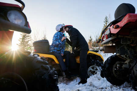 Couple in love sitting on yellow all-terrain vehicle and kissing. Young woman and man in helmets holding glasses of champagne and sharing tender moment on winter day. Concept of love and quad biking. Foto de archivo