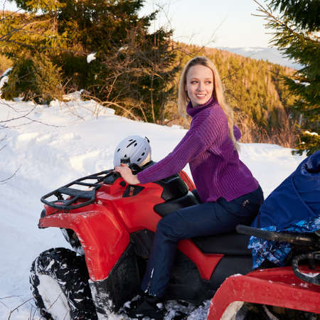 Side view of beautiful female rider in sweater sitting on red quad bike. Charming woman looking aside and smiling while driving all-terrain vehicle in winter mountains. Concept of winter activities.