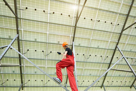 Young electrician connecting electrical cables inside the lit by sun solar modules. Ecology power conservation concept. Green ecological power energy generation. Banco de Imagens