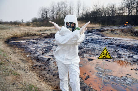 Scientist wearing white protective coverall and gas mask standing next to biohazard sign at contaminated water. Man crossing his hands stop visitors. Do not enter, dangerous area, stay where you are Archivio Fotografico