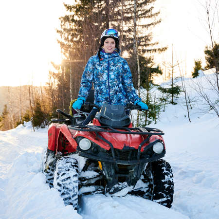 Portrait of charming woman in winter jacket and goggles enjoying quad biking in winter mountains. Joyful female traveler on all-terrain vehicle smiling to camera. Concept of winter sport activities Foto de archivo