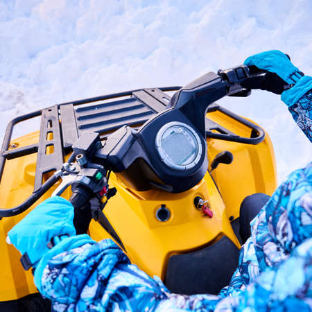 Close up of female hands in blue waterproof sport mittens driving all-terrain vehicle. Woman rider holding handlebars of yellow quad bike with white snow on background. Concept of quad biking. Foto de archivo