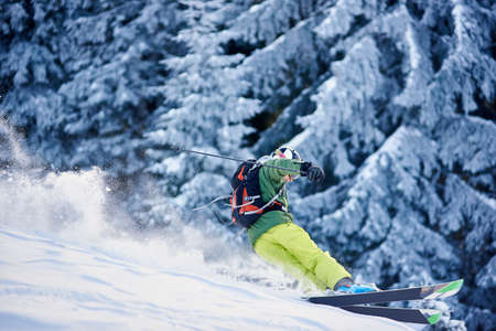 Skier with backpack doing freeride-descent on snow-covered slope in white snow powder blizzard. Dangerous maneuvering on mountain wooded downhill. Picturesque forest scenery on blurred background. Stock Photo