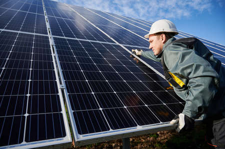Professional worker, wearing protective suit, helmet and gloves, installing a photovoltaic solar batteries on a sunny day. Concept of alternative energy and power sustainable resources.