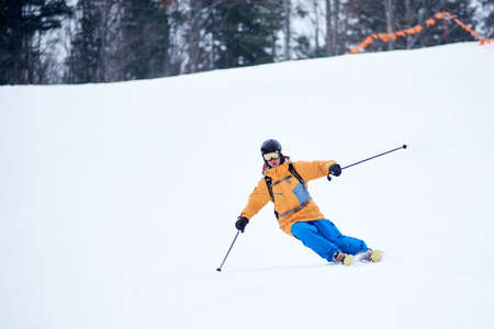 Professional skier concentrated on skiing down on steep ski slope. Proficient technical carving skiing. Net on slope edge. Wooded mountain top on background. Extreme winter activities concept Stockfoto