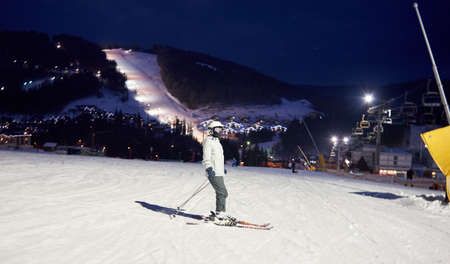 Side view of female unrecognizable skier in ski mask after skiing day standing on skis. Evening pastime at resort. Fairy illuminated mountain countryside view and chairlift in darkness on background.