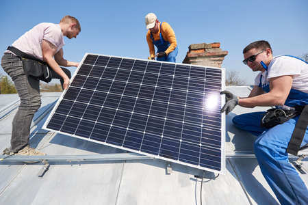 Male team workers installing solar photovoltaic panel system. Three electricians lifting blue solar module on roof of modern house. Sustainable resources innovation environmental concept.
