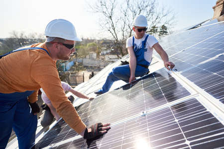 Male engineers installing solar photovoltaic panel system. Electricians mounting blue solar module on roof of modern house. Alternative energy ecological concept.
