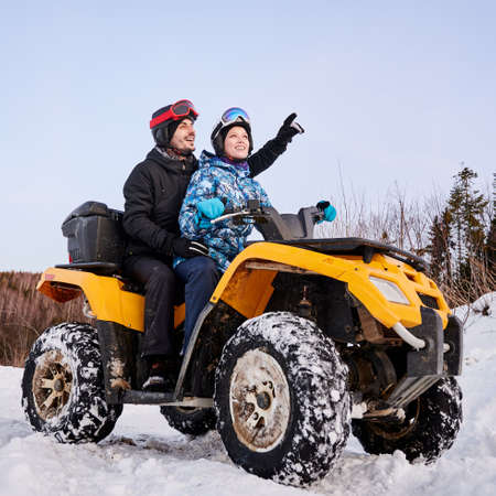 Side view of joyful young woman and man in helmets sitting on all-terrain vehicle. Handsome male traveler pointing at something and smiling while riding quad bike with woman in winter mountains.