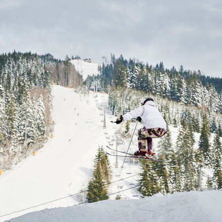 Male skier in winter jacket and helmet skiing downhill in snowy mountains with beautiful snowy trees and hills on background. Man freerider on skis making jump while sliding down snow-covered slope Stock fotó