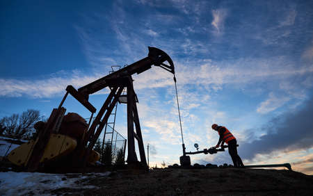 Silhouette of petroleum operator in work vest and helmet using oil pumping unit to extract crude oil from oil well, working in oil field with pump jack under beautiful sky.