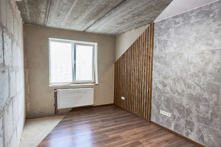 Comparative image of room before and after repairs. Unfinished walls made of blocks, ceiling vs shiny finished walls and wood floor. Concept of home restoration and renovation. Stock Photo