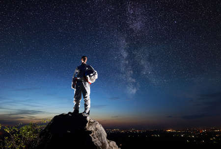 Space traveler standing on top of rocky hill and looking at beautiful sky with stars. Astronaut in white space suit holding helmet. Concept of space travel and cosmonautics.