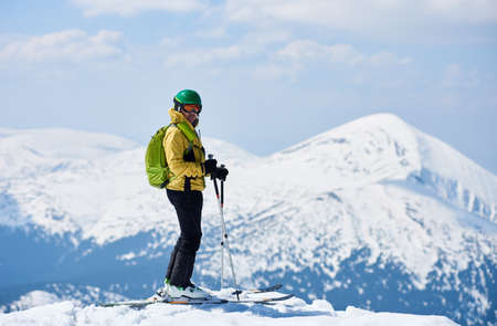 Sporty man enjoying skiing day and spectacularly view mountain landscape under blue sky Snow and winter activities, skitouring in mountains.