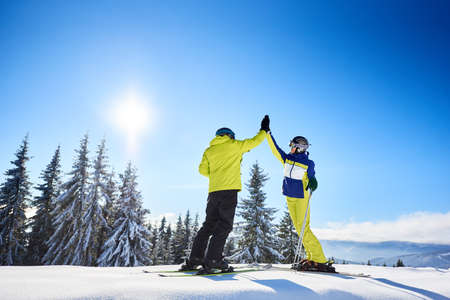 Couple high-five to each other under sunny blue sky high in mountains. Skiers after successful skiing up to mountain top. Coniferous forest on background. Happiness, success, common goal concept.
