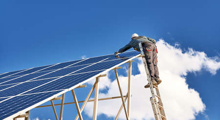 Horizontal snapshot of a male worker wearing a uniform, standing on a ladder on the top of a solar plant, mounting solar modules on a sunny day. Clear blue sky and one white cloud on background