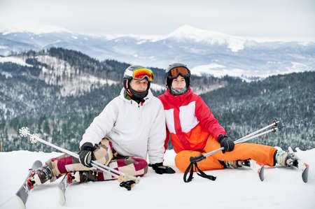 Two friends wearing ski suits and ski equipment are in winter mountains enjoying snowy weather, skiing and incredible landscapes. Portrait of a couple sitting on snowy hill smiling looking at camera Stock Photo