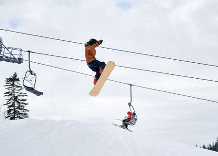 Guy snowboarder doing tricks in the mountains in winter season, flying up high with snowboard against ski lift and cloudy sky. Low angle view. Concept of winter kinds of sport, extreme sport.