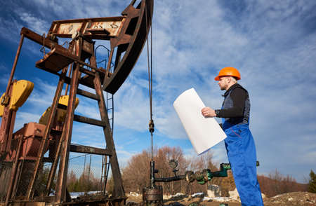 Side view of oil worker holding plan of oil field at petroleum pump jack. Drill operator in work uniform and helmet standing near oil pumping unit. Concept of petroleum industry and oil extraction.
