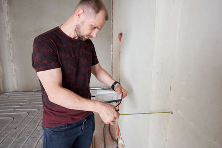 Close-up snapshot of young professional in empty unfinished apartment measuring the wall with a help of measure tape, verifying notes. Repairs and refurbishment concept 版權商用圖片