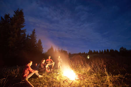 Group of friends sitting near campfire in high green grass, illuminated tent at night camp in the mountains, surrounded by spruce trees under magical starry sky. Concept of summer activities, camping