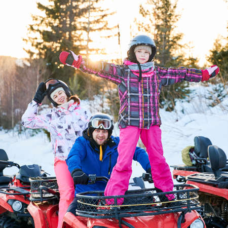 Young family in helmets smiling to camera while sitting on all-terrain vehicle with cute daughter. Adorable little girl in winter jacket enjoying quad biking with parents. Concept active leisure. Foto de archivo