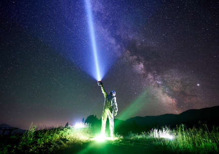 Spaceman wearing white space suit and helmet directs a blue ray of light into sky full of stars with a help of lantern in the night in the mountains, standing on illuminated green grass. Space concept