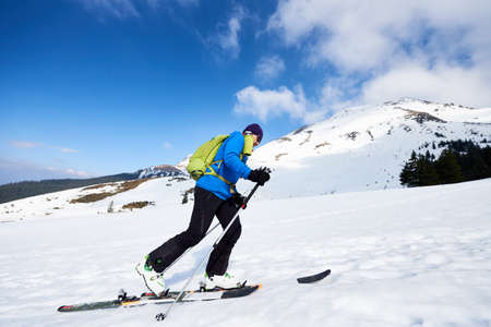 Happy tourist in colorful clothing and sunglasses with backpack climbing on skis in deep snow on background of bright blue sky and beautiful mountain. Winter vacations, active lifestyle concept.