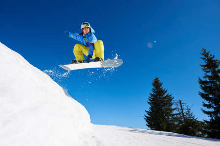 Jumping snowboarder keeps one hand on the snowboard on blue sky background. Ski season and winter sports concept