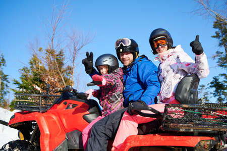 Young man and woman showing victory gesture and thumbs up while sitting on quad bike with adorable daughter. Girl sitting on all-terrain vehicle with parents. Concept of family and active leisure.