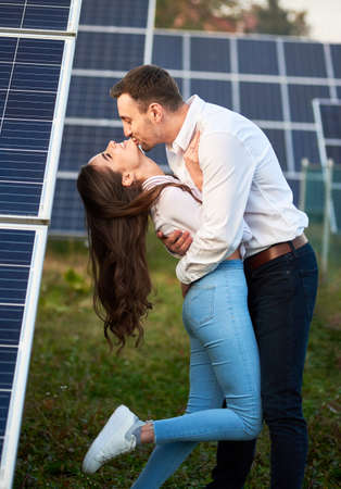 A man kisses his lover against the background of a series of solar panels. A woman with long hair is enjoying the arms of a loved one. A modern world with continuously advancing technology 免版税图像