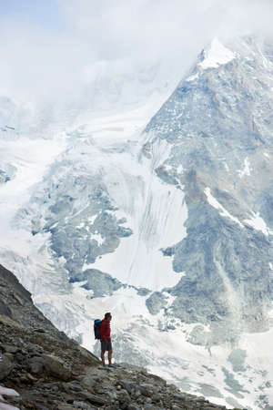 Vertical snapshot of incredibly beautiful mount in Swiss Alps - Ober Gabelhorn, man standing on a slope enjoying a cold quiete scenery. Concept of freedom, mountain hiking, tourism and alpinism