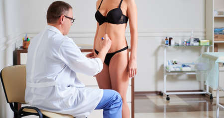 Male doctor drawing marks on female body before plastic surgery. Woman standing in front of surgeon while man drawing line on her bare skin. Concept of plastics and preparation for aesthetic surgery. 版權商用圖片