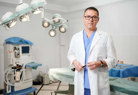 Front view of man surgeon in glasses looking at camera with serious expression while standing in operating room in the hospital. Concept of medicine, medical workers and plastic surgery.