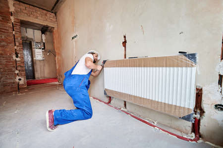 Plumber in work overalls using wrench while installing heating radiator in room. Man in helmet installing heating system in apartment. Concept of radiator installation, plumbing works, home renovation 版權商用圖片