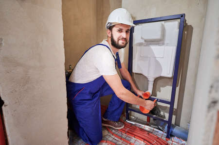 Handsome bearded man in work overalls installing concealed toilet frame in bathroom. Cheerful male worker in safety helmet looking at camera and smiling while installing wall-hung toilet system.