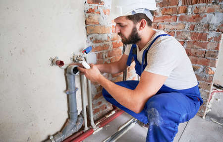 Young plumber, wearing blue uniform and white helmet working with sealant fix of sewer pipe in kitchen or in bathroom in unfinished apartment. Concept of plumbing works and home renovation 版權商用圖片