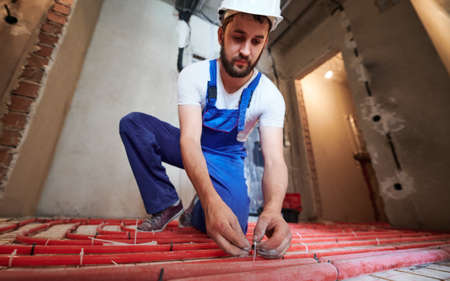 Bearded young man in safety helmet installing pipes for warm floor in apartment. Male plumber in work overalls installing underfloor heating system. Focus on the hands. Concept of home renovation.
