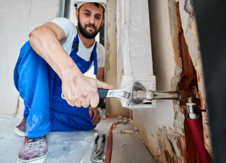 Bearded young man in work overalls using plumber wrench while installing heating radiator in room. Male plumber in safety helmet installing heating system in apartment. Focus on hand with instrument.