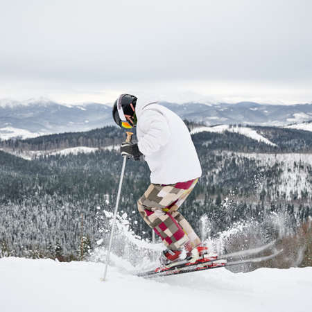 Back view of alpine skier in jacket and helmet skiing on fresh powder snow in winter mountains. Man freerider making jump while sliding down snow-covered slopes at ski resort. Motion blur 版權商用圖片