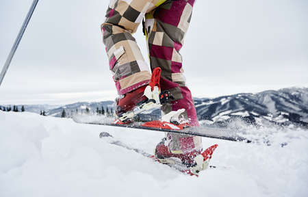 Close-up cropped snapshot of skiers legs, ski fastening and skis, making step forward, ski tour. Low angle view. Winter sports concept 版權商用圖片