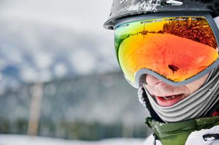 Close-up cropped snapshot of man wearing ski goggles with reflection of snowed slope. Bright glasses reflecting nature in winter. Concept of active lifestyle