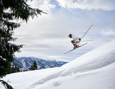 Side view of male skier making jump while sliding down snow-covered slope on skis under beautiful cloudy sky. Man freerider in helmet skiing on fresh powder snow in mountains. 版權商用圖片