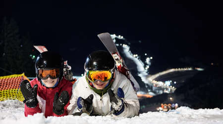 Couple of tourists lying on snowy slope at night, resting after active time spending on ski pistes. Close-up portrait of two cheerful happy people on snow