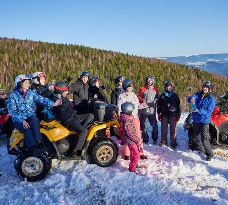 Group of cheerful people sitting on four-wheelers ATV, enjoying beautiful winter day in snowy mountains, uncorking bottle of blue champagne. Celebration outdoors. Concept of active lifestyle