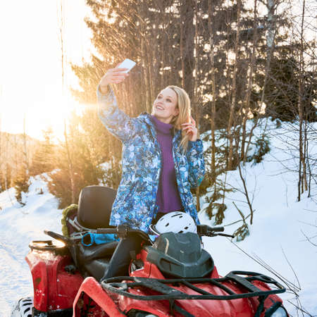 Joyful blonde woman in winter jacket taking picture with smartphone during quad biking in winter mountains. Charming female traveler on all-terrain vehicle looking at phone camera and smiling.