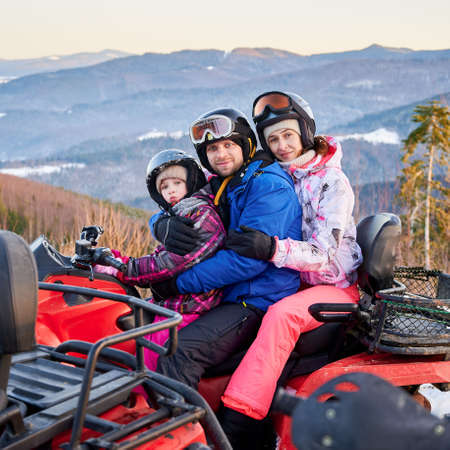 Portrait of happy family of three, wearing colorful ski suits, spending great winter holiday, hugging together in snowy mountains on red quad bike, side view, ridge of mountains on background