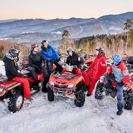 Yaremche, Ukraine - February 02, 2020: Group of men sitting on ATV bikes, having small talks and laughing on cold winter day in snowy mountains, mountain ridge on background. Concept of friendship