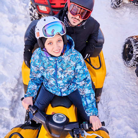 Top view of joyful young woman and man in helmets and goggles driving all-terrain vehicle through snow. Female and male riders looking at camera and smiling while sitting on quad bike.