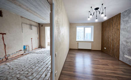 Two empty rooms with modern plastic window, heating radiators and heating inderfloor pipes before and after renovation. Comparison of old room and new renovated place with parquet, stylish chandelier 版權商用圖片